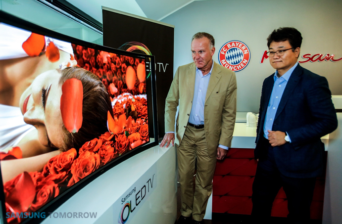 Karl Heinz Rummenigge, CEO, FC Bayern Munich and Dongmin Kim, VP, Head of Samsung Electronics Germany check out the exceptional picture quality on Samsung's Curved OLED TV